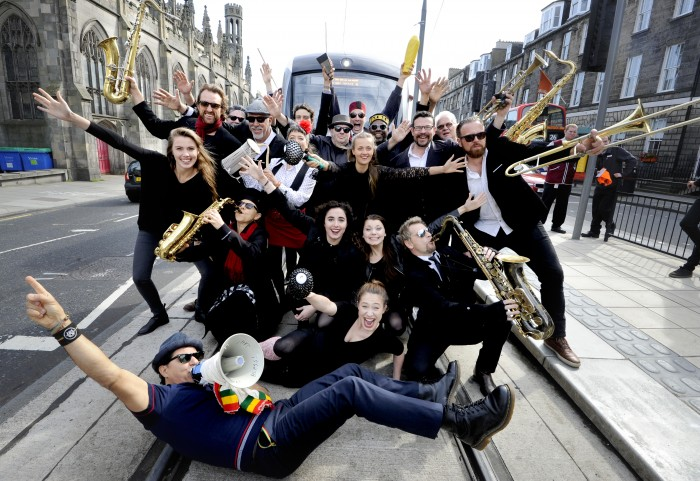 FREE PICTURE: Melbourne Ska Orchestra at Edinburgh Fringe, Mon 08/08/2016: Orchestral Manoeuvres on the Trams – Ska Conga Delights Commuters. More than a dozen musicians from the Melbourne Ska Orchestra joined up with Fringe visitors to form a ska conga on the Edinburgh trams. The band, which includes Kilmarnock singer Steven Montgomery who is performing in Scotland for the first time after leaving for Oz 20 years ago, are at the Fringe to promote their latest album Sierra-Kilo-Alpha. They entertained festival-goers and commuters at York Place while they waited for a tram to take them across the city. Melbourne Ska Orchestra peforma at 1800 nightly until Friday (12th August 2016) at the Teviot Hall Gilded Balloon. Lead singer Nicky Bomba leads the band across the tram tracks at York Place. More information from: Matthew Shelley PR - 07786 704 299 - MJHShelley@hotmail.co.uk Photography for ……. from: Colin Hattersley Photography - www.colinhattersley.com - colinhattersley@btinternet.com - 07974 957 388. Free FIRST USE (ONLY) picture. Photography from: Colin Hattersley Photography - colinhattersley@btinternet.com - www.colinhattersley.com - 07974 957 388